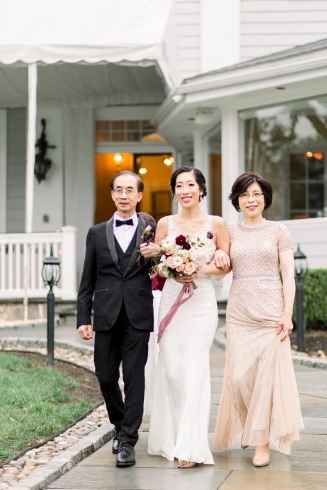 The bride and her parents walking down the aisle