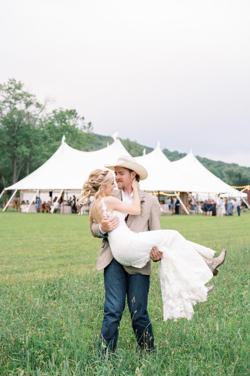 groom carries bride in wedding photos