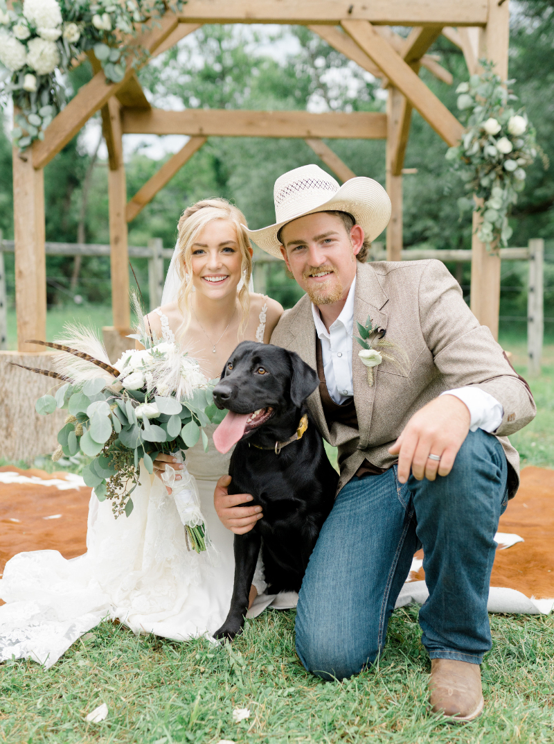 bride and groom pose with their dog