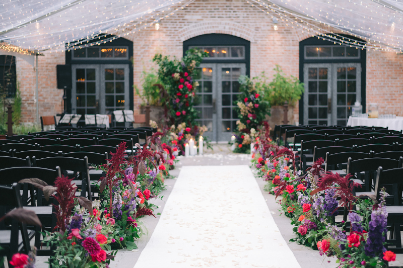 Colorful pink purple and red floral wedding ceremony